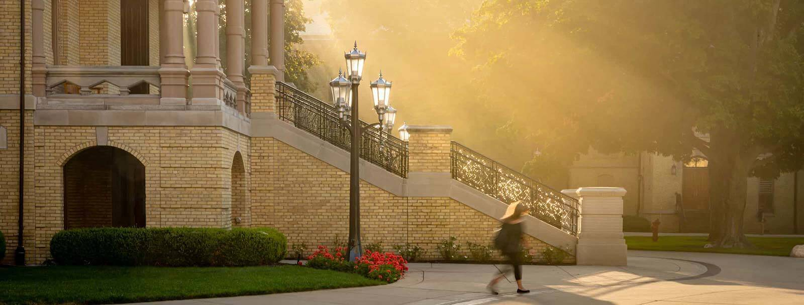 A person walks behind the Main Building steps during a misty sunrise.
